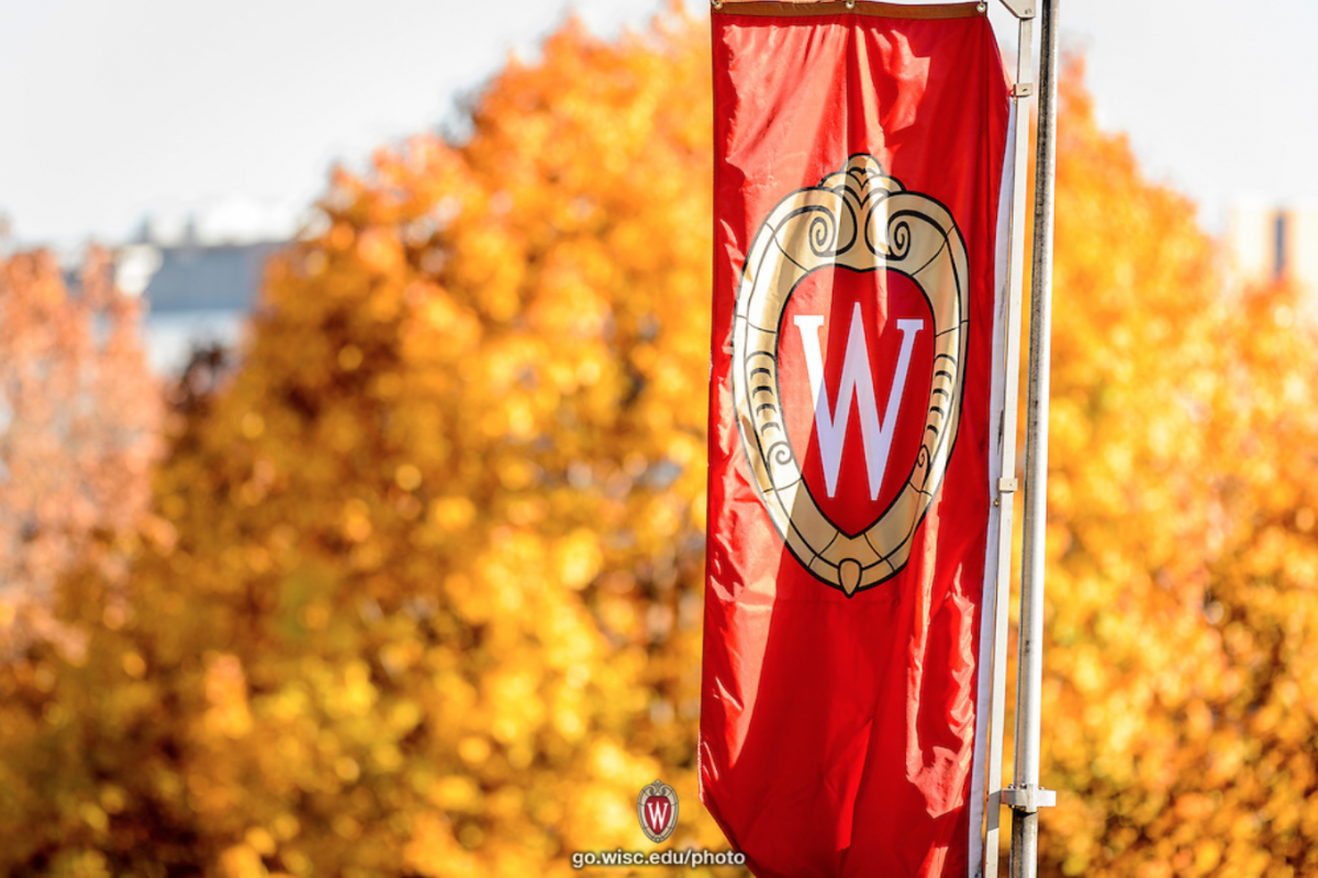"In the foreground, there is a red banner with the University of Wisconsin's ""W"" crest. Behind the banner there are several trees with yellow, gold, and orange fall foliage. A glimpse of the lake is between the trees."